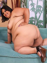 Young plumper demonstrates her curves on sofa